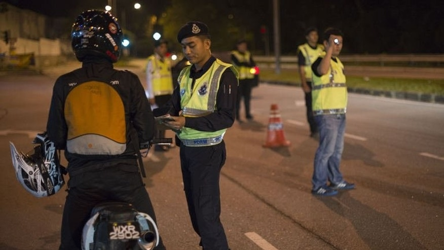 "A Malaysian policeman checking a motorcyclist's identification papers at a roadblock during an operation called ""Op Cantas Khas"" in Kuala Lumpur on August 21, 2013. A wave of lethal shootings is rattling normally laid-back Malaysia and raising new doubts about the much-maligned national police force's ability to protect the public."