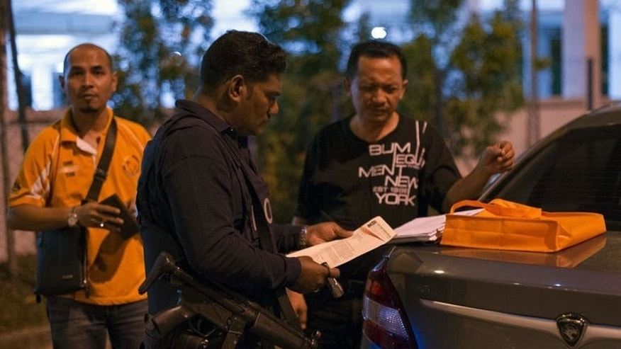 "Malaysian policemen check a driver's identification papers at a roadblock during an operation called ""Op Cantas Khas"" in Kuala Lumpur on August 21, 2013. Near-daily gun violence in recent weeks in a country with tough firearms restrictions has sown fear and confusion, and triggered a weekend police crackdown widely considered long overdue."