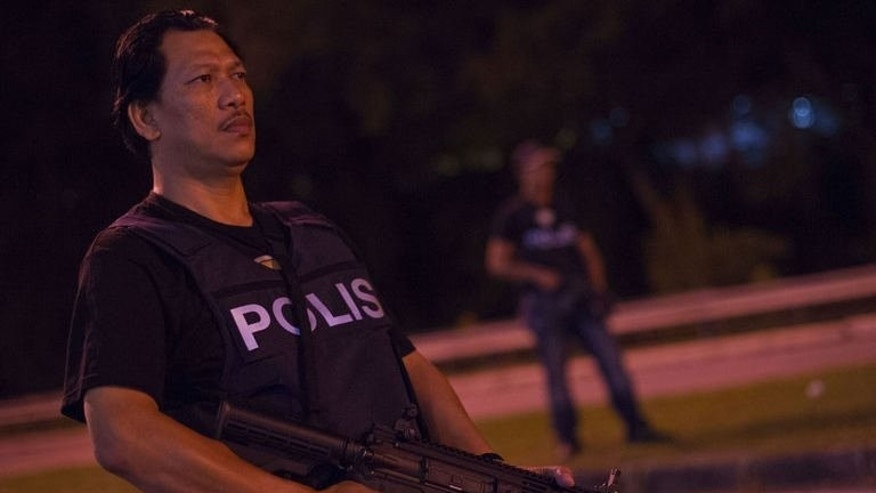 "A Malaysian policemen guards a roadblock during an operation called ""Op Cantas Khas"" in Kuala Lumpur on August 21, 2013. The mentality of the police force is little changed from its early years fighting a failed communist insurrection in the 1950s, said opposition legislator Liew Chin Tong."