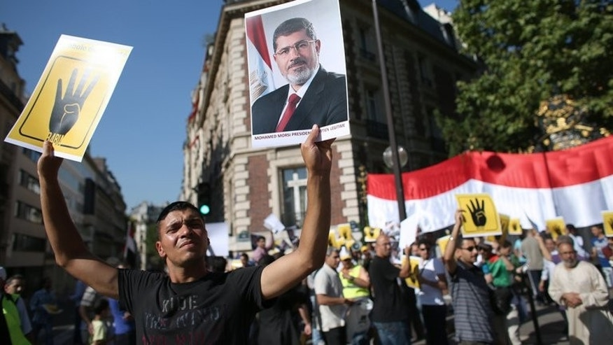 "A protester holds a placard reading ""R4BIA"" (L) and a poster of Egypt's ousted president Mohamed Morsi during a protest against army-installed Egyptian government, in front of the Saudi Arabia's embassy in Paris, on August 20, 2013. Europe stood poised to firmly condemn the blistering violence in Egypt but stop short of sanctions as EU foreign ministers gathered Wednesday."