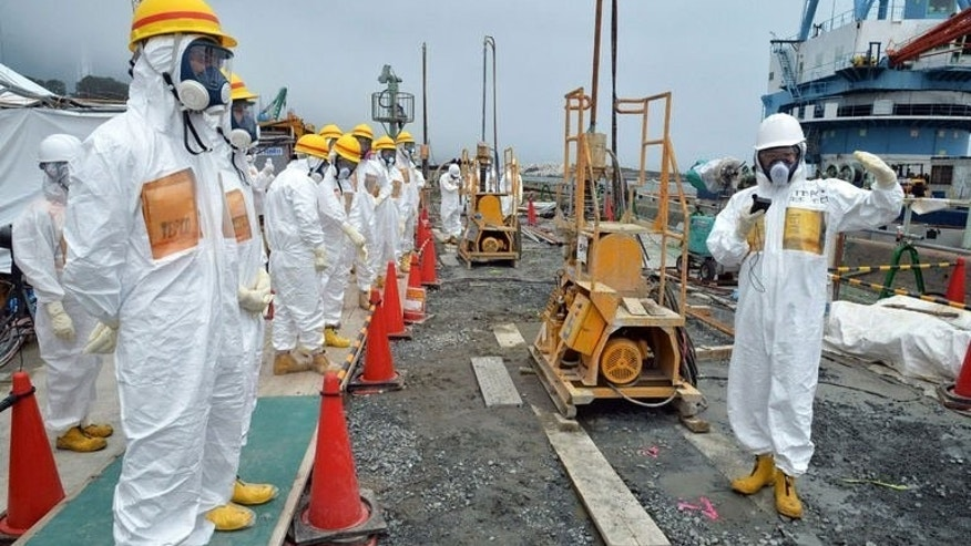 "Government officials and nuclear experts inspect a construction site set up to prevent the seepage of contaminated water into the sea, at the Fukushima nuclear plant on August 6, 2013. Japan's nuclear regulator upgraded a radioactive water leak at the crippled Fukushima plant to a level three ""serious incident"" Wednesday, its highest warning in two years."