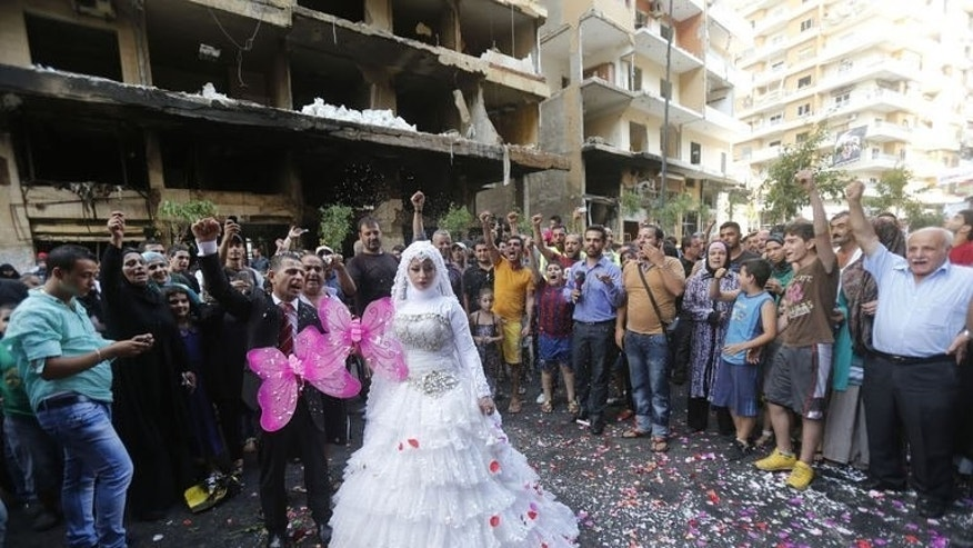 "People cheer as a bride and groom pose for pictures on August 18, 2013 at the site of a car bomb explosion in Beirut's Rweiss neighbourhood that killed at least 27 people on August 15. Shiite militant group Hezbollah was already accused of running a ""state-within-a-state,"" but two car bombings in the area in as many months have spurred them to turn the suburbs into a fortress."