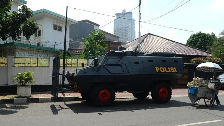An Indonesian police armored vehicle (C) stands posted outside the Myanmar embassy compound (back L) in Jakarta before the arrival of anti-Myanmar demonstrators on May 3, 2013. Indonesian police have arrested four men suspected of involvement in a failed plot to bomb the Myanmar embassy in Jakarta, an official said Wednesday.