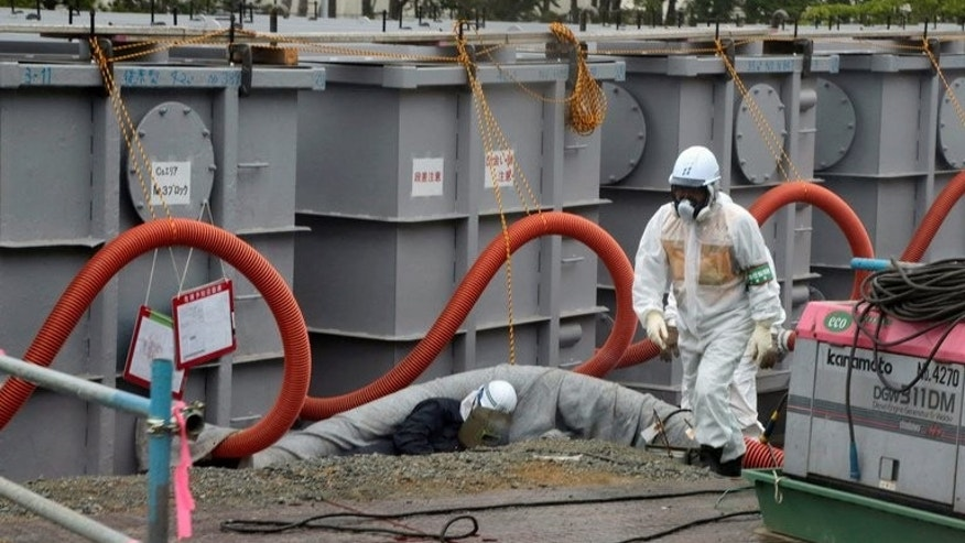 "File picture shows a Tokyo Electric Power Co (TEPCO) worker next to waste water tanks at Japan's Fukushima Daiichi nuclear plant on June 12, 2013. Japan's nuclear regulator on Wednesday upgraded its evaluation of a radioactive water leak at the crippled nuclear plant in Fukushima to a level three ""serious incident""."