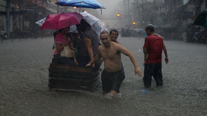 Residents wade through a flooded street in Manila on August 20, 2013. Heavy rain pounded the Philippine capital and surrounding areas for a third day Wednesday, adding to the misery of nearly 300,0000 exhausted people displaced from their flooded homes.