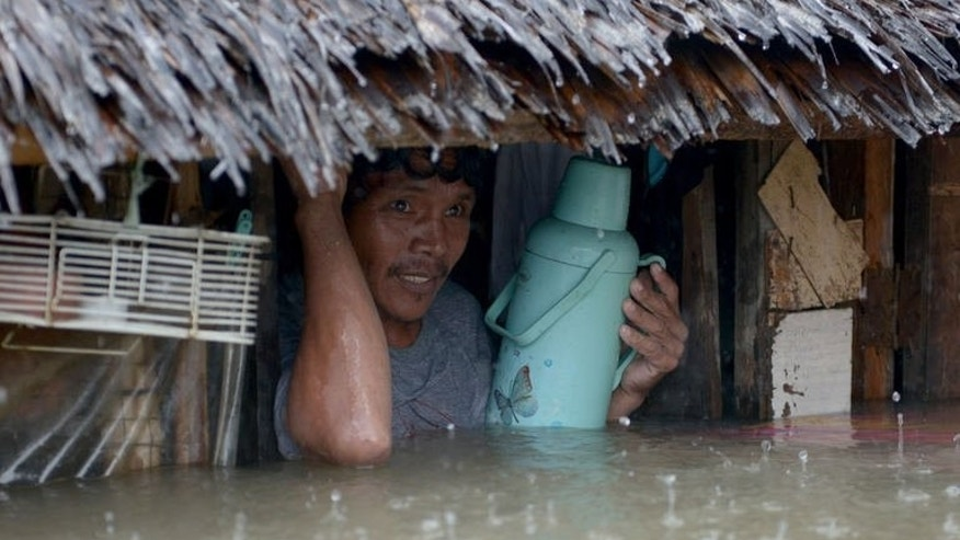 A resident prepares to leave his flooded home in the farming town of Novaleta, some 26 kilometres outside Manila on August 19, 2013. Eight people have already been confirmed killed from the monsoon rains that have battered the main Philippine island of Luzon
