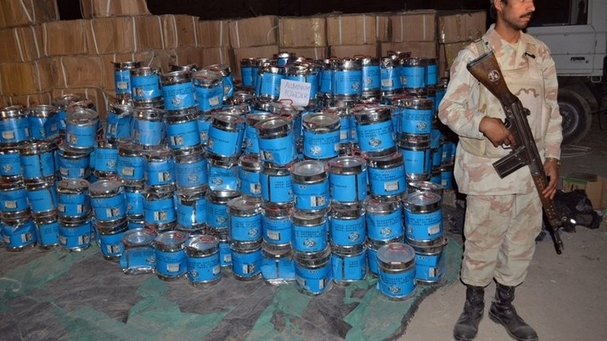 A Pakistani paramilitary soldier stands beside the seized bomb making material in Quetta on August 20, 2013. Pakistani authorities said Wednesday that a car bomb factory where troops confiscated more than 100 tones of chemicals had been used in recent attacks on troops and minority Shiite Muslims.