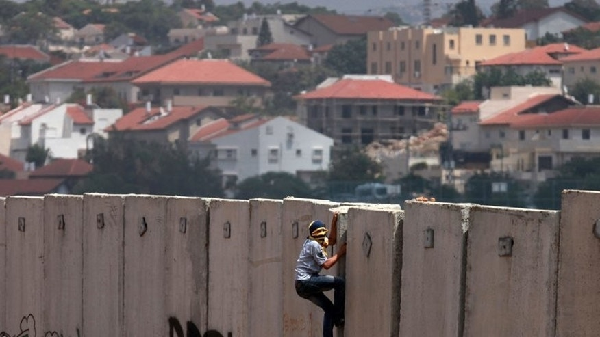 A Palestinian protester climbs Israel's separation barrier in the West Bank village of Nilin on June 14, 2013. The Palestinians threatened Wednesday to sue Israel through international bodies if it continues expanding settlements in the occupied territories, warning it was an issue that could torpedo fledgling peace talks.