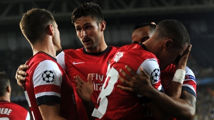 Arsenal's players celebrate with teammate Kieran Gibbs (R) after he scored a goal against Fenerbahce during their UEFA Champions League Play Off first leg match at Sukru Saracoglu Stadium in Istanbul on August 21, 2013. Arsenal won 3-0.