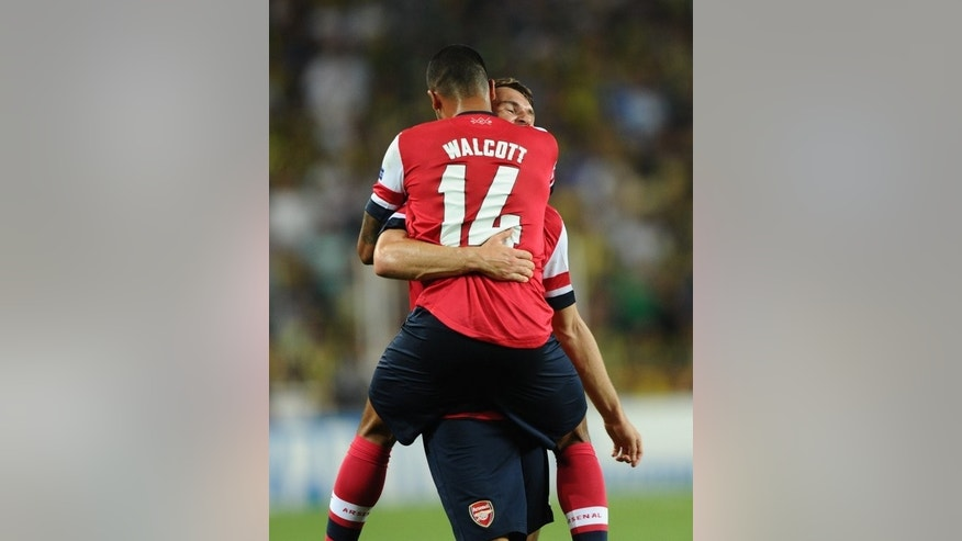 Arsenal's Aaron Ramsey celebrates with Theo Walcott after scoring the second goal against Fenerbahce during their UEFA Champions League Play Off first leg match at Sukru Saracoglu Stadium in Istanbul on August 21, 2013. Arsenal won 3-0.