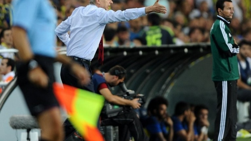 Arsenal's head coach Arsene Wenger reacts during their match with Fenerbahce's Raul Meireles (R) during their UEFA Champions League Play Off first leg match at Sukru Saracoglu Stadium in Istanbul on August 21, 2013. Arsenal won 3-0.