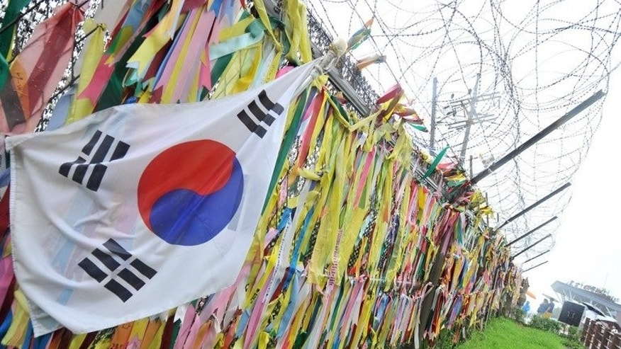Ribbons carrying messages wishing for the reunification of the two Koreas, hang on a military fence at Imjingak peace park in Paju near the demilitarized zone dividing the two Koreas on July 23, 2013. South Korea's pointman on North Korea on Wednesday played down expectations of any imminent turnaround in inter-Korean relations following a recent flurry of movement on cross-border projects.