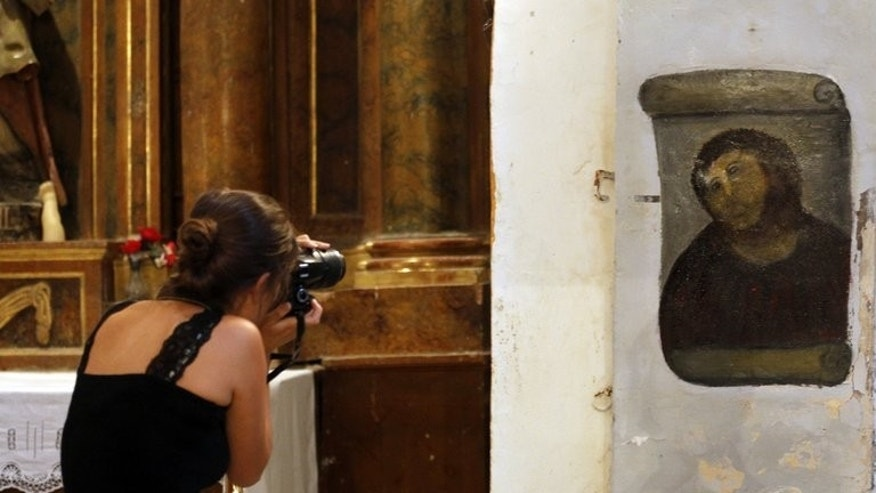 A woman takes pictures of the 'restored' Ecce Homo painting at Borja Church in Zaragoza last August. Cecilia Gimenez took it upon herself a year ago to fix up Ecce Homo (Behold the Man), a flaking, century-old fresco of Christ painted on a pillar in a church in Borja, northeastern Spain.