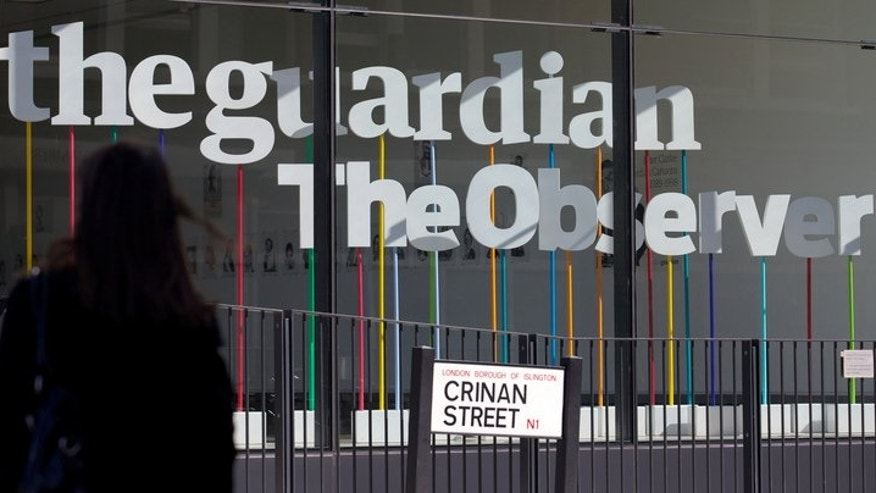A woman walks past the offices of the Guardian newspaper in central London on August 20, 2013. Britain's top civil servant approached The Guardian to demand the newspaper return or destroy secret files leaked by former US intelligence analyst Edward Snowden, reports said Wednesday.