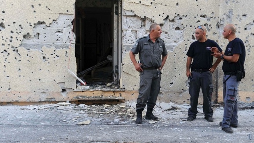 Aug. 22, 2013: Israeli policemen stand in front of a house damaged by a rocket fired from Lebanon in Shavei Tzion outside Nahariya in northern Israel. Military spokesman Lt. Col. Peter Lerner said Thursday that three rockets landed in northern Israel, while one was shot down.