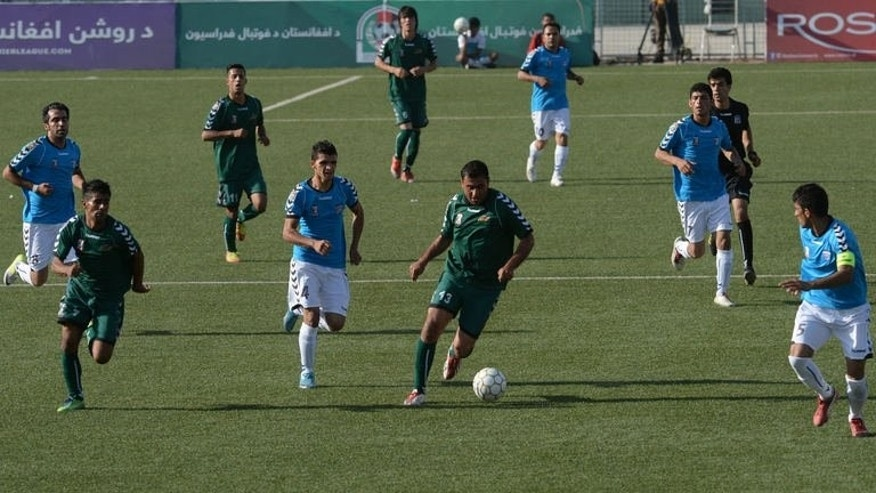 Afghan footballers from Tofaan Harirod (blue jerseys) and Spinghar Bazan (green jerseys) fight for the ball during game of the Roshan Afghan Premiere League at the Afghanistan Football Federation stadium in Kabul on August 22, 2013. Afghanistan's second season of domestic league football opened with eight sides competing in a tournament.