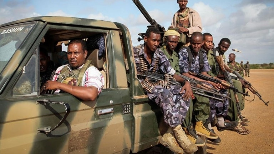 Fighters belonging to the pro-government Ras Kimboni Brigade ride on the back of a machine mounted truck at the Kismayo Airport in southern Somalia on August 22, 2013. African troops in Somalia said they thwarted an attack Thursday by Islamist Shebab fighters on their base in the southern port city of Kismayo.