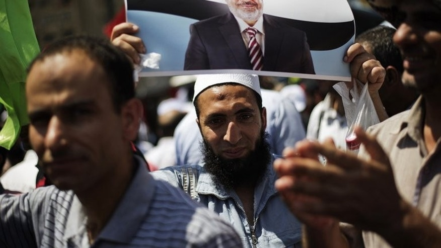 A protester is seen with a picture of President Mohamed Morsi as Islamists and Muslim Brotherhood supporters gather at the Rabaa al-Adawiya mosque in Cairo, on June 28, 2013. The ouster of Morsi, a member of the Muslim Brotherhood, has now set off something of a witch hunt against those perceived as being his supporters.