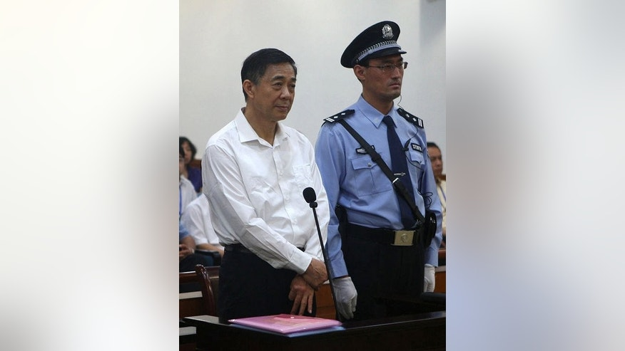 Former Chinese political star Bo Xilai (L) stands on trial in the Intermediate People's Court in Jinan, China, on August 22, 2013, in a photo released by the Jinan Intermediate People's Court's Weibo account