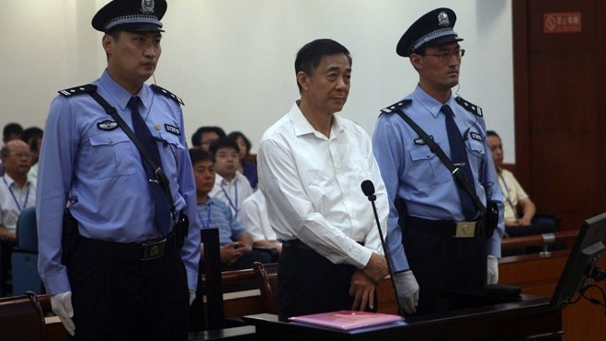 Aug. 22, 2013: In this photo released by the Jinan Intermediate People's Court, Bo Xilai, center, stands on trial at the court  in eastern China's Shandong province.