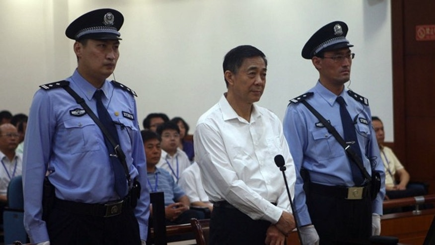Aug 22, 2103: In this photo released by the Jinan Intermediate People's Court, Bo Xilai, center, stands on trial at the court  in eastern China's Shandong province.