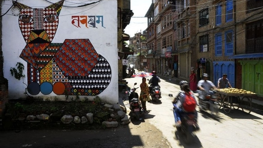 Nepalese travel past a mural in Kathmandu on August 20, 2013. Nepal's capital has been given a facelift thanks to a team of artists who have painted dozens of elaborate and metres-high murals on walls around the Himalayan city.