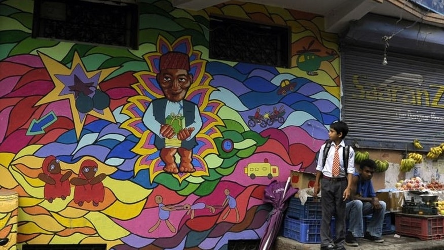 """A Nepalese schoolboy looks at a mural while standing beside a vegetable vendor in Kathmandu on August 20, 2013. Some 60 artists have been involved in the project called """"Kolor Kathmandu"""" which began in January and will culminate on Thursday with the launch of a book of photographs on the murals."""