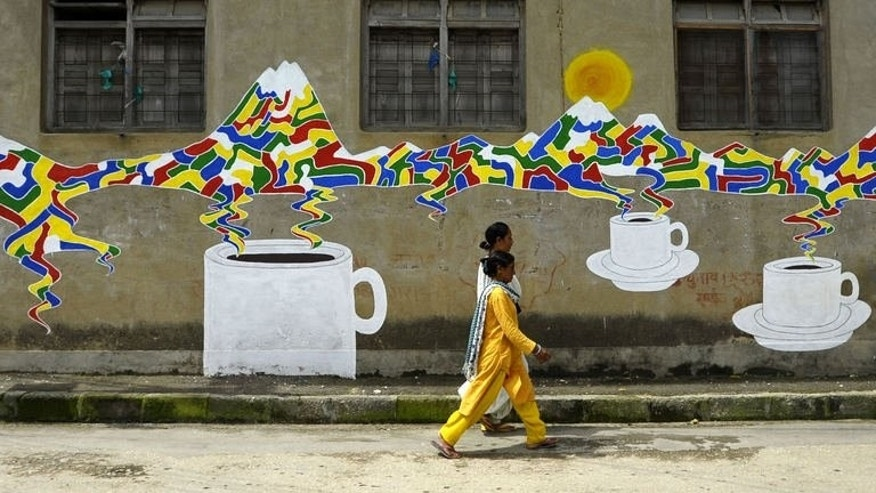 Nepalese walk past a mural in Kathmandu on August 20, 2013. Nepal's capital has been given a facelift thanks to a team of artists who painted dozens of elaborate and metres-high murals on walls.