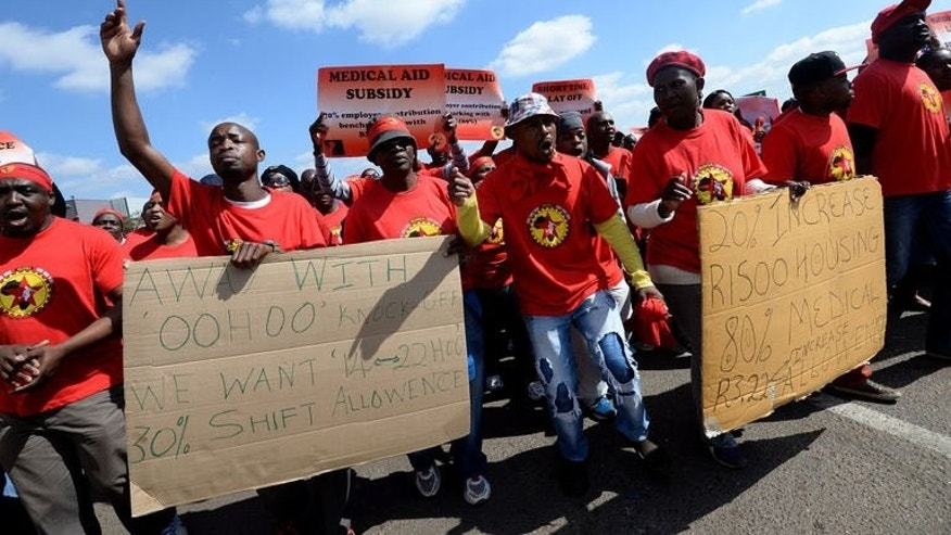 Workers on strike hold signs as they take part in a demonstration outside Ford's plant in Pretoria on August 20, 2013. Strikes loomed in key South African sectors Thursday after wage talks stalled in the continent's largest economy.