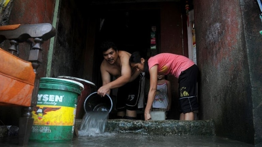 Residents bail floodwater from their house in Noveleta, Cavite, south of Manila on August 21, 2013. Philippine National Red Cross secretary-general Gwendolyn Pang said floods have receded in all but about 10 percent of the Manila metropolis of 12 million people.