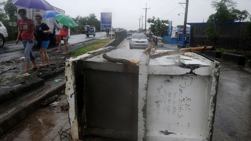 Residents walk past tombs washed away by flood waters at a street in Noveleta, Cavite, south of Manila on August 21, 2013.