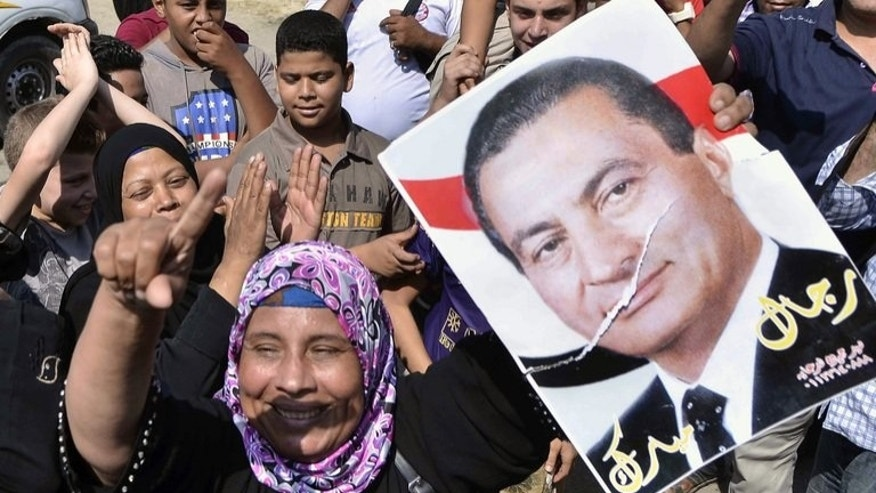 An Egyptian supporter of former president Hosni Mubarak raises his portrait outside the Tora prison in Cairo on August 22, 2013. Mubarak was flown from prison by helicopter to a military hospital Thursday after he was cleared for conditional release while standing trial, an interior ministry general told AFP.