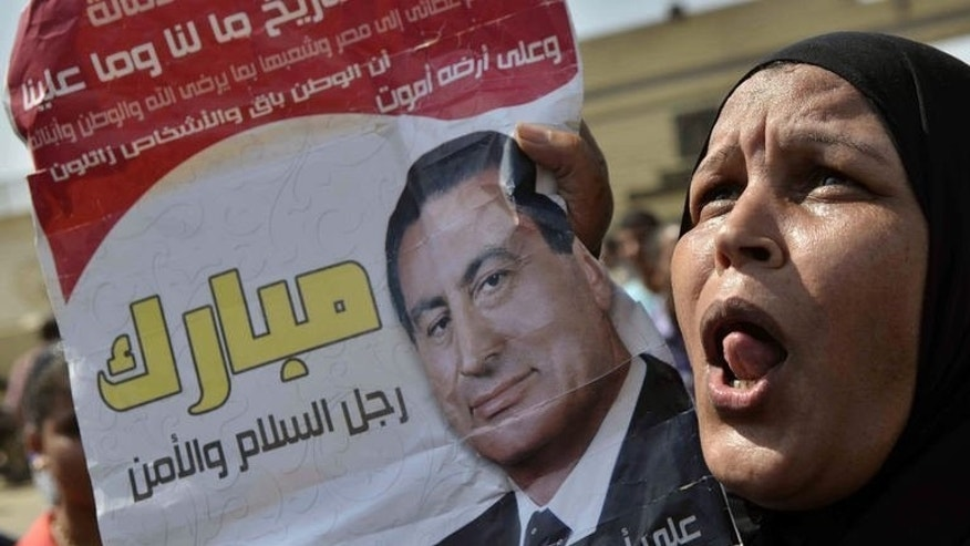 A supporter of former Egyptian president Hosni Mubarak ululates as she holds up his portrait outside the Tora prison in Cairo where Mubarak is detained, on August 22, 2013. Mubarak, who left jail for house arrest on Thursday, enjoyed near absolute power for three decades as president before a 2011 uprising overthrew him.