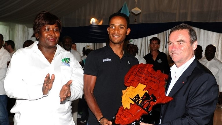 Eritrea's Natnael Berhane (C) receives the African Cyclist of the year 2012 trophy from Bernard Hinault (R), five-times Tour de France champion, at the Beach Club in Libreville, on January 20, 2013. Berhane is only one of several Eritreans in this cycling-mad Horn of Africa state making his mark on the sport.