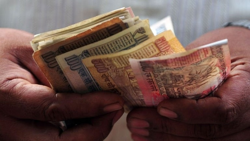 An Indian counts rupee notes in Mumbai on August 19, 2013. India's rupee tumbled to a new record low against the dollar on Thursday as uncertainty about the future of the US stimulus programme added to growing fears about the state of the Indian economy.