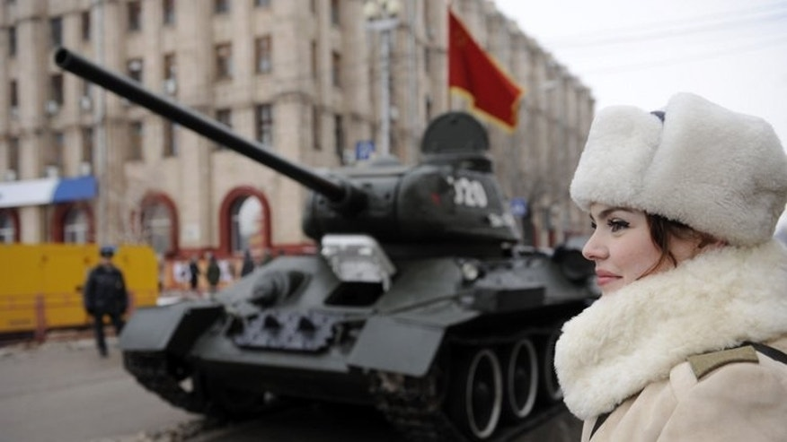"A woman watches a military parade in Volgograd in February marking the anniversary of the Stalingrad battle. ""What can one do in penniless Volgograd? The city became scary, old. It has decayed,"" says Yelena Isinbayeva."