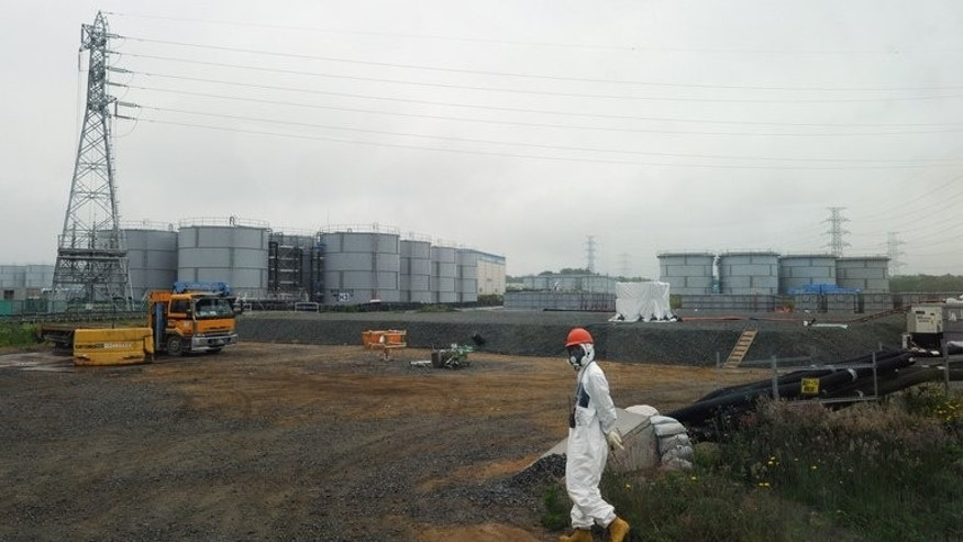 A construction worker walks near water tanks at Japan's Fukushima Daiichi nuclear plant, on June 12, 2013. The country's nuclear watchdog has dispatched a team of investigators to examine a toxic water leak at the facility.