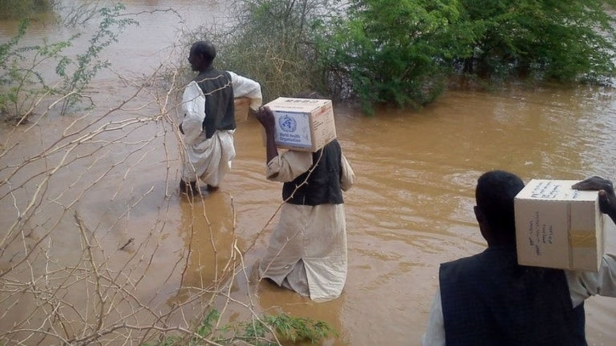 A picture distributed by WHO on August 22, 2013 shows WHO staff and volunteers carrying boxes of medicines and supplies while they cross flooded areas to reach a health facility in Aroma district, Kassala, East Sudan on August 15, 2013. More than 300,000 people across Sudan have been affected by floods which killed almost 50 people this month.