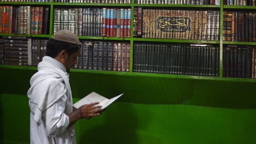 A Pakistani student reads a book at the Ganj Islamic seminary in Peshawar, August 21, 2013. The Pakistani madrassa, slapped with US sanctions for being an alleged terror training centre, has denied the charges, insisting it teaches only religion and Arabic grammar to around 150 boys.