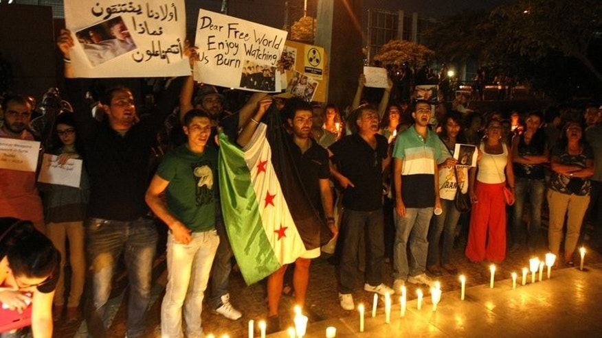 Lebanese and Syrian civilians hold a candlelit vigil in front of the UN headquarters in Beirut, in solidarity with Syrian civilians killed in attacks in the suburbs of Damascus on August 21, 2013. Syrian forces blasted rebel zones near Damascus on Thursday, including areas where the opposition alleged loyalists had launched a chemical weapons attack a day earlier, a monitoring group said.