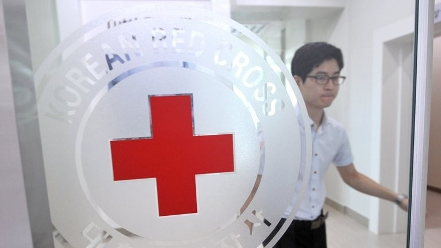 A South Korean man walks past a logo of the Red Cross at its office in Seoul on August 22, 2013. Red Cross officials from the two Koreas will hold talks as planned Friday in resuming cross-border family reunions after the North finally agreed to the South's choice of venue.