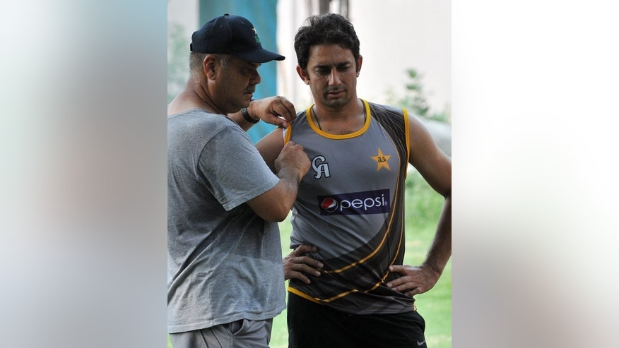 In this file photo, Pakistan's coach Dav Whatmore (L) is seen with team player Saeed Ajmal, in Lahore, on July 5, 2013. Pakistan won every match on their last tour of Zimbabwe in 2011, and will expect to complete a similar sweep over a side that recently lost all five one-day internationals against an understrength Indian team.