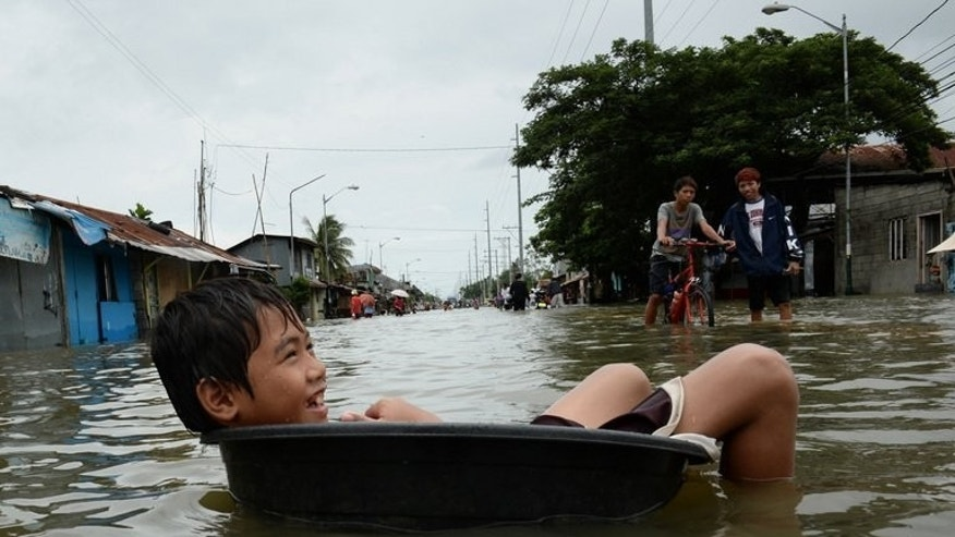 A boy uses a plastic basin to float along a flooded street in the town of Calumpit, north of Manila, on August 22, 2013. The official death toll from the floods has been raised to 20.