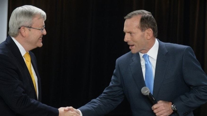 Australia's Prime Minister Kevin Rudd (L) and oppostion leader Tony Abbott (R) at the start of a people's forum debate in Brisbane on August 21, 2013. Abbott says he would pay Indonesians for unseaworthy boats to stop them falling into the hands of people-smugglers.