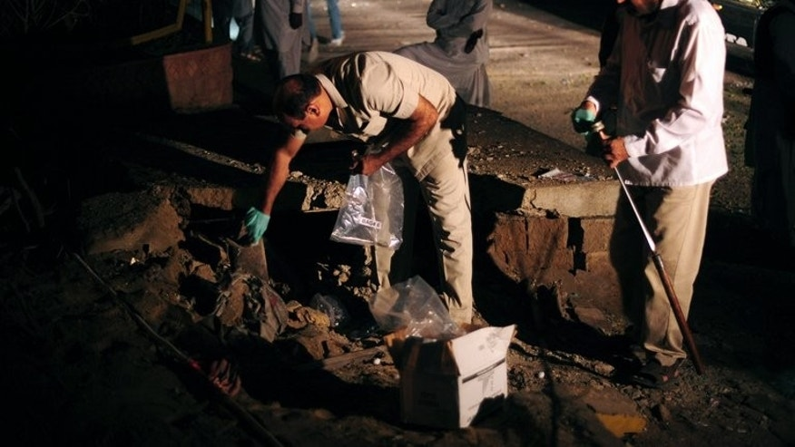 Pakistani security officials collect evidence at the site of a bomb explosion in Karachi on August 22, 2013. The death toll rose to two after a wounded soldier died.