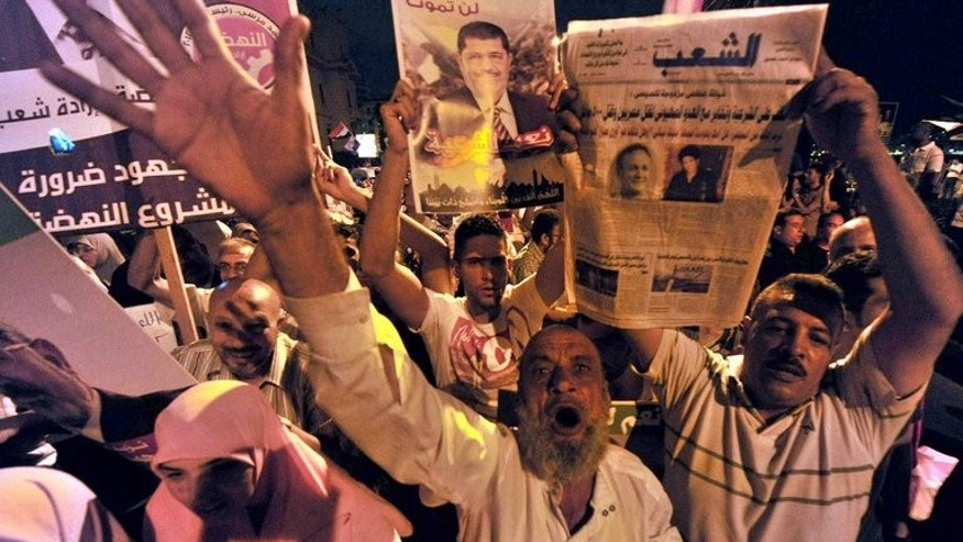 Muslim Brotherhood supporters shout slogans as they wave portraits of Egypt's ousted president Mohamed Morsi during a demonstration in the port city of Alexandria on August 13, 2013.