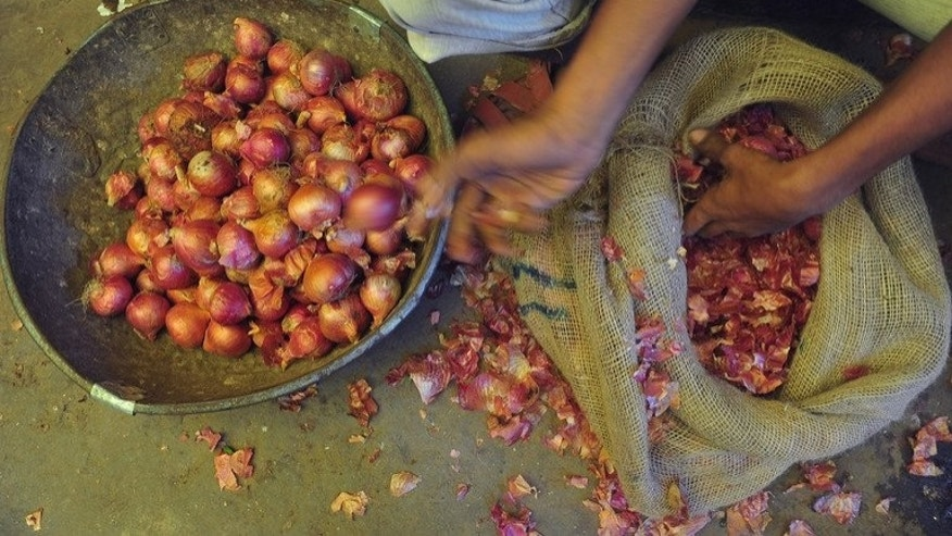 A youth select onions from a sack at a market in Mumbai on August 22, 2013. Food grains, fruits and vegetables worth $6.8 billion go to waste every year in India because of inadequate storage facilities, a minister said on Friday.