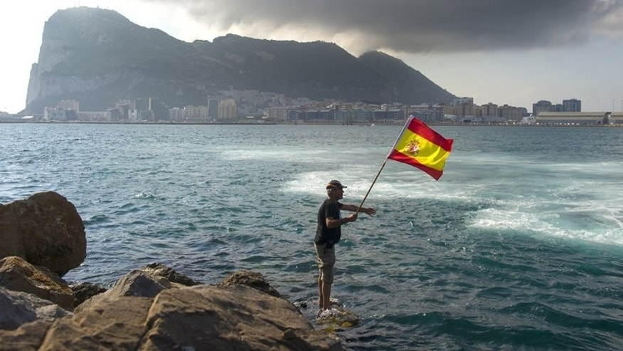 "A fisherman holds a Spanish flag during a protest in the bay of Algeciras near Gibraltar on August 18. Chief Minister Fabian Picardo said he planned to allow the 59 fishing boats operating in the area from the neighbouring Spanish ports of La Linea and Algeciras to return to their traditional fishing grounds near the ""Rock""."