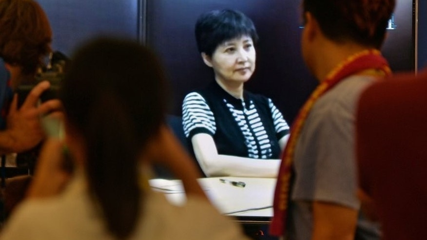 "Journalists look at a broadcast of Gu Kailai (C), who is the wife of disgraced politician Bo Xilai, as she gives recorded testimony during his trial at the Intermediate People's Court in Jinan, Shandong Province on August 23, 2013. Fallen Chinese politician Bo Xilai described his wife as ""insane"" Friday after his corruption trial heard video testimony from her implicating him in bribery."