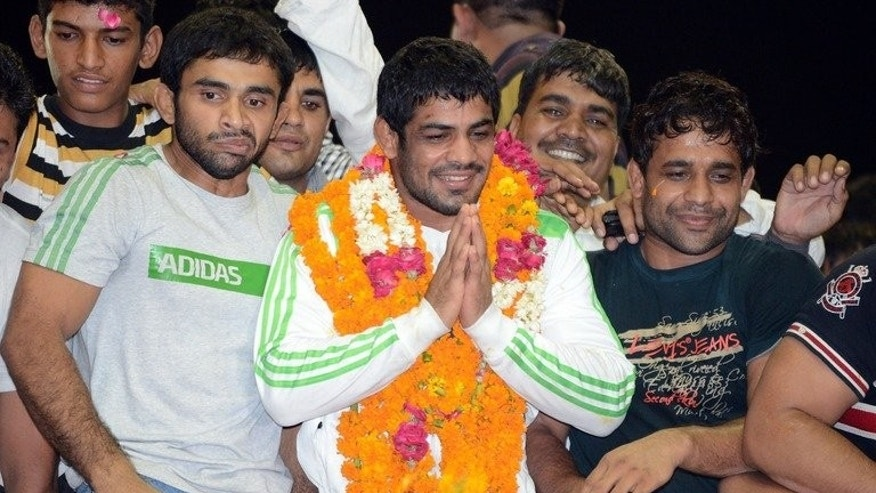 Indian wrestler Sushil Kumar (C), at IGI airport in New Delhi on August 13, 2012. He told a newspaper he was offered money to lose a world championship title bout in Moscow in 2010.